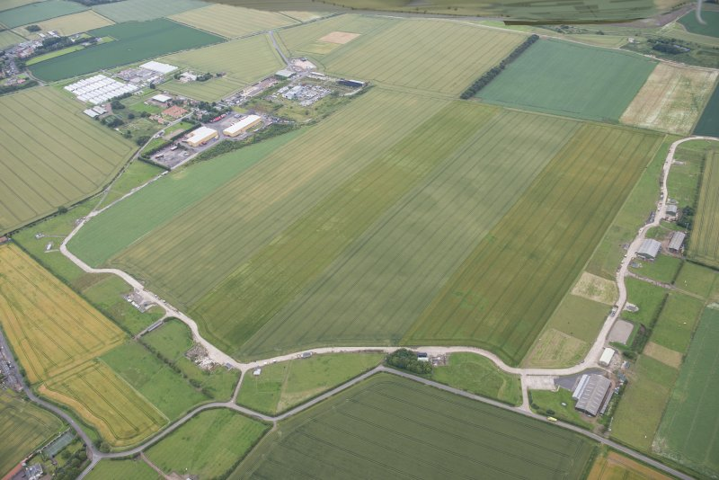 General oblique aerial view of Drem Airfield and the cropmarks of the palisaded enclosure and pit defined boundary, looking SSE.