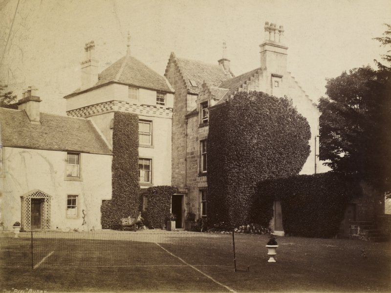 View of The Peel, Busby from south east showing a tennis court at the back of house