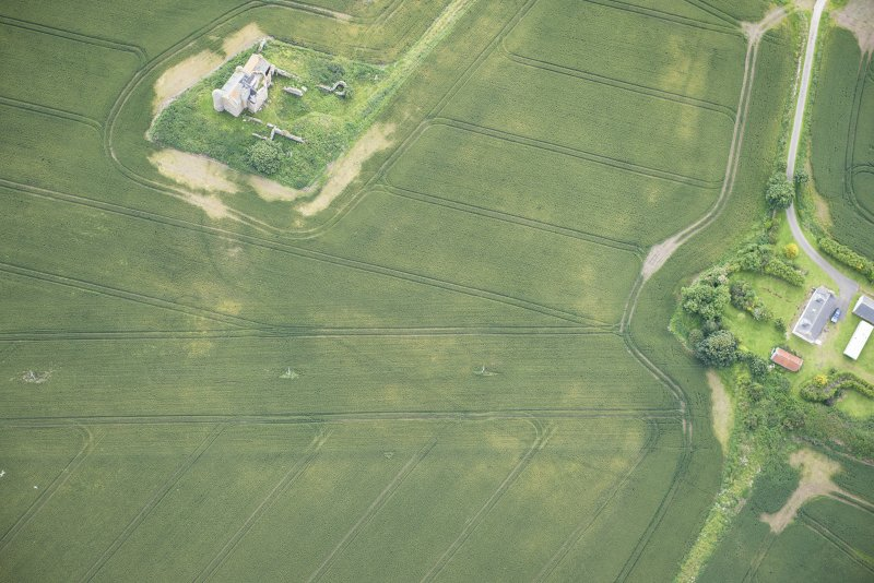 Oblique aerial view of Inchdrewer Castle and the cropmarks of the ditch, looking SE.