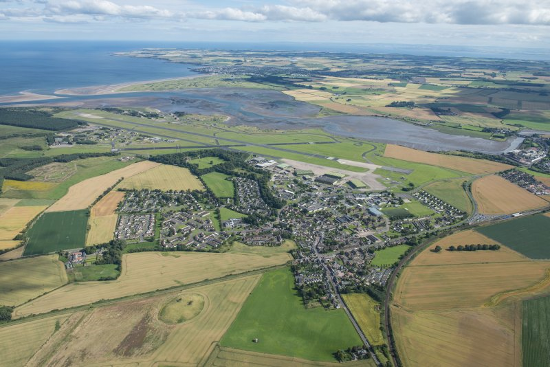 General oblique aerial view of Leuchars village and airfield with the Eden Estuary Nature Reserve beyond, looking SE.