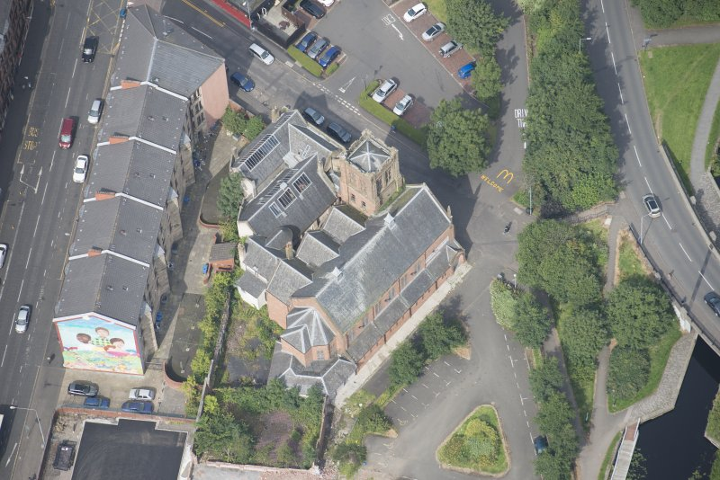 Oblique aerial view of Ruchill Parish Church and Ruchill Parish Church Hall and Janitor's House, looking NW.
