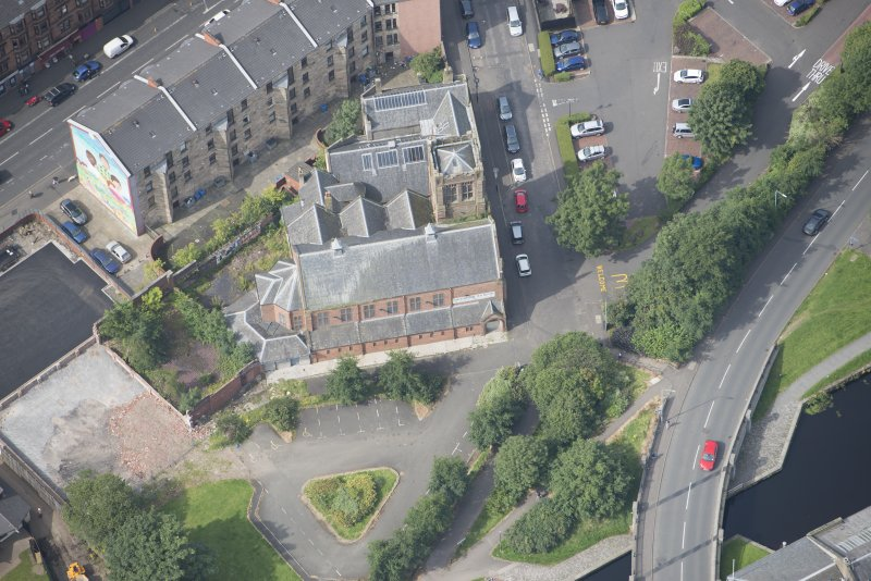 Oblique aerial view of Ruchill Parish Church and Ruchill Parish Church Hall and Janitor's House, looking W.
