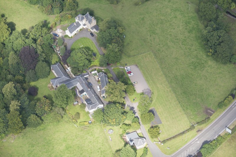 Oblique aerial view of Peel Lodge, Tower House and Stables, looking NW.