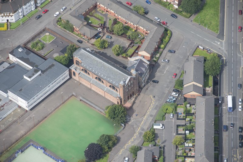 Oblique aerial view of Sacred Heart Church and Presbytery, looking N.