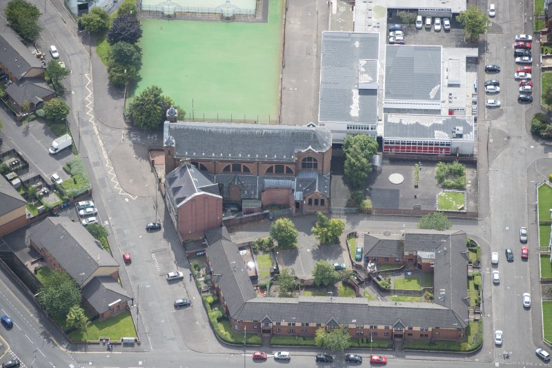 Oblique aerial view of Sacred Heart Church and Presbytery, looking S.