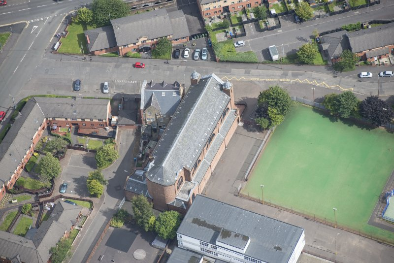 Oblique aerial view of Sacred Heart Church and Presbytery, looking E.