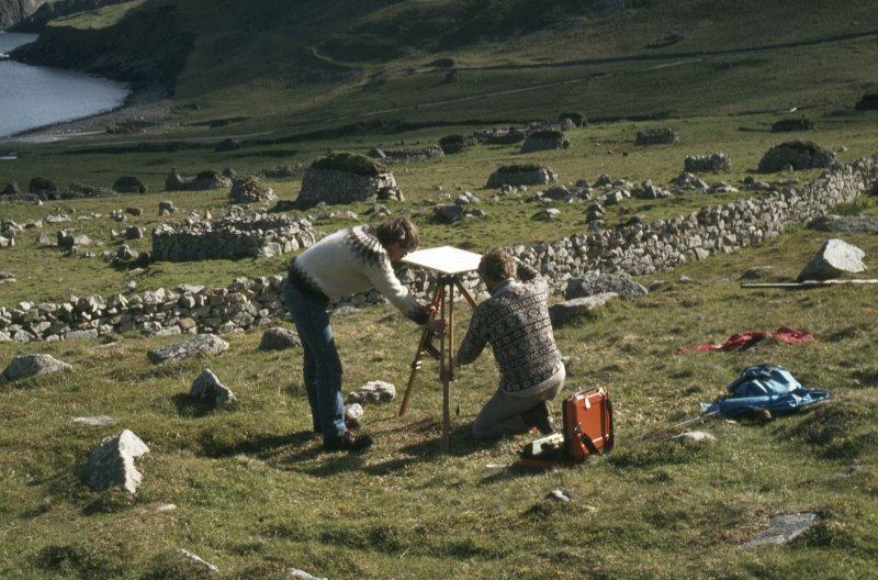 Alan Leith and Sam Scott (RCAHMS Surveyors) setting up a plane table during the survey of Village Bay, St Kilda. Copied from a slide in the collection of G Stell.