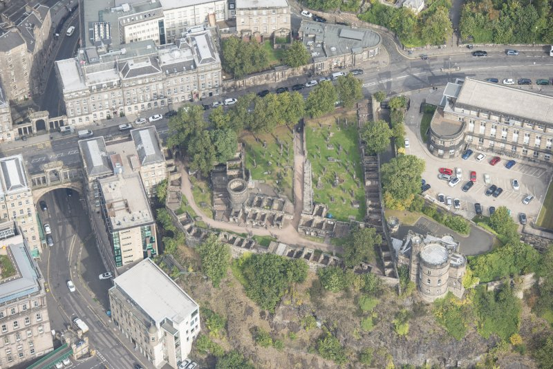 Oblique aerial view of Governor's House at St Andrew's House, Regent Bridge and Old Calton Burial Ground, looking N.