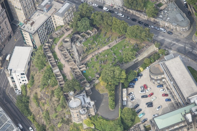 Oblique aerial view of Governor's House at St Andrew's House, Regent Bridge and Old Calton Burial Ground, looking NW.