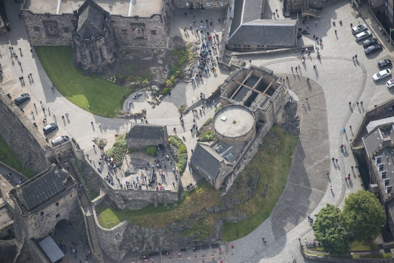 Oblique aerial view of Edinburgh Castle centred on St Margaret's Chapel,  looking S.