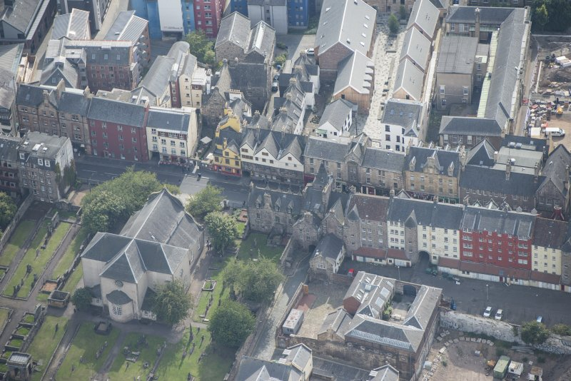 Oblique aerial view of the Canongate, Canongate Tolbooth, Canogate Parish Church and Huntly House, looking SSE.