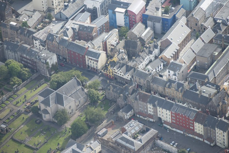 Oblique aerial view of the Canongate, Canongate Tolbooth, Canogate Parish Church, Moray House and Huntly House, looking SE.