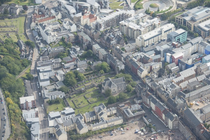 Oblique aerial view of the Canongate, Canogate Parish Church and Moray House, looking ESE.