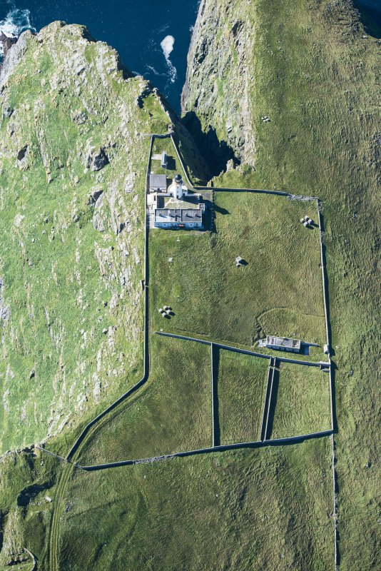 Oblique aerial view of Barra Head Lighthouse, the field boundaries and the possible dun, looking W.