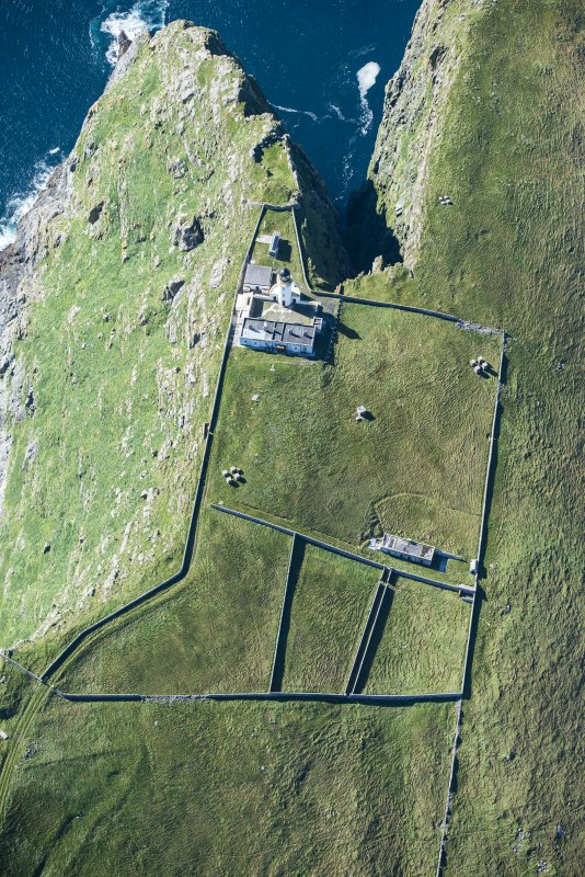Oblique aerial view of Barra Head Lighthouse, the field boundaries and the possible dun, looking WSW.