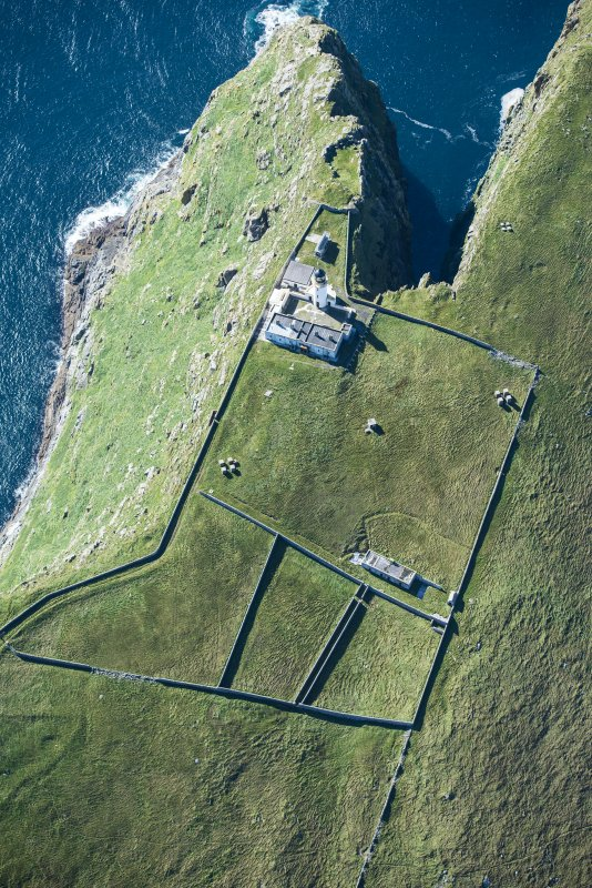 Oblique aerial view of Barra Head Lighthouse, the field boundaries and the possible dun, looking SW.