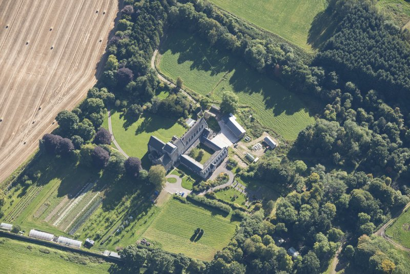 Oblique aerial view of Pluscarden Abbey, looking E.