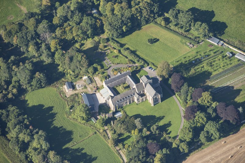 Oblique aerial view of Pluscarden Abbey, looking W.