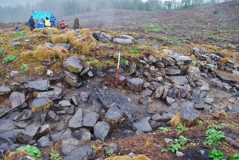 Post-excavation image of north facing section of Trench 1, showing possible collapsed stonework in the dun entrance, areas of burning and outer wall face structure, Comar Wood Dun, Cannich, Strathglass