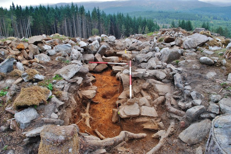 Trench 2 half-section, cleaned to 212 natural, and probable inner face of dun wall in centre back of image, Comar Wood Dun, Cannich, Strathglass