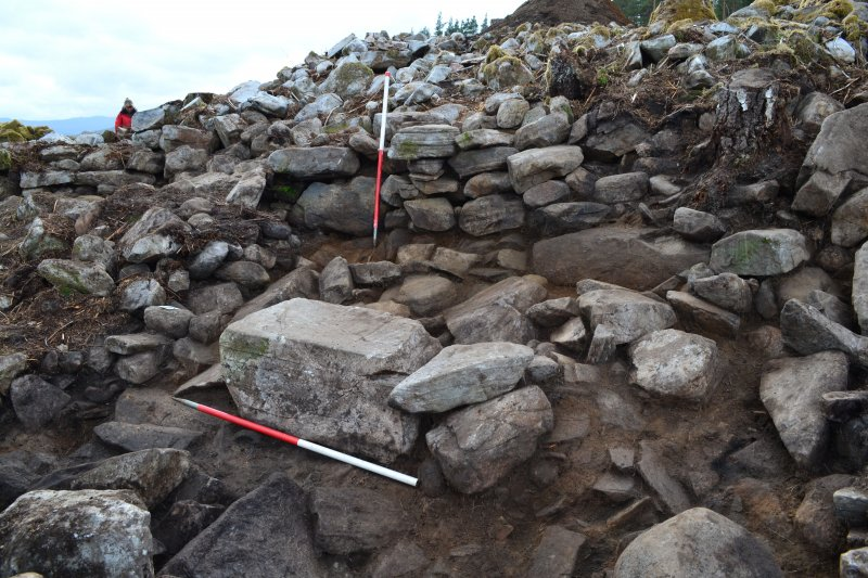 East facing dun outer wall and blocked passage (marked by upright scale pole); large recumbent boulder in front may have formed part of an exterior wall, Comar Wood Dun, Cannich, Strathglass