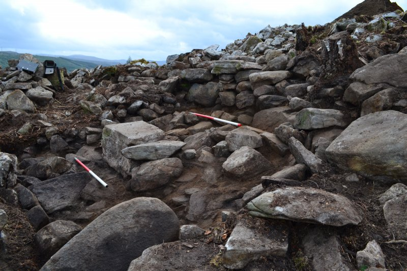 Mid-excavation image after initial clean-back showing blocked passage in the outer wall (top centre) and possible external wall base (left centre); image shows large displaced slab in left foreground, which may be a displaced slab from the external wall, Comar Wood Dun, Cannich, Strathglass