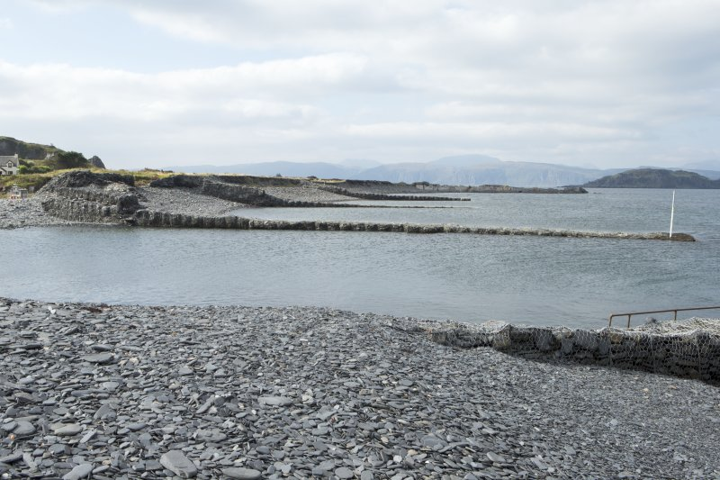 Shingle beach and slate waste filled gabion piers, view from south east