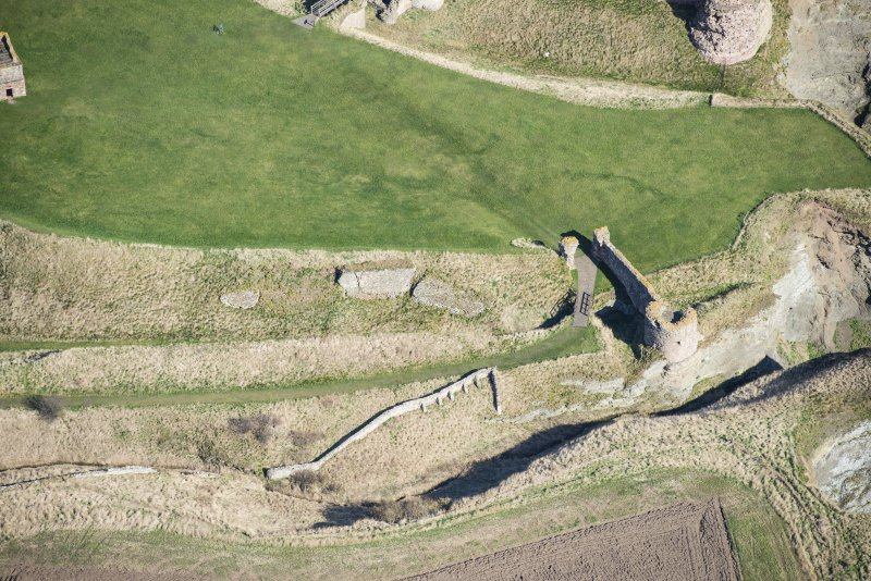 Oblique aerial view of the entrance through the outerworks at Tantallon Castle, looking NNE.