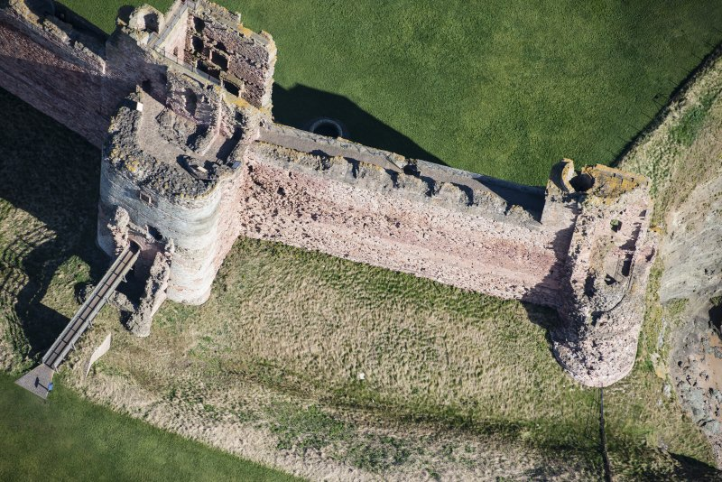 Oblique aerial view of the Mid Tower and East Tower at Tantallon Castle, looking NNE.