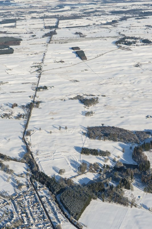 Oblique aerial view of the Roman fort and road at Ardoch, looking NNE.