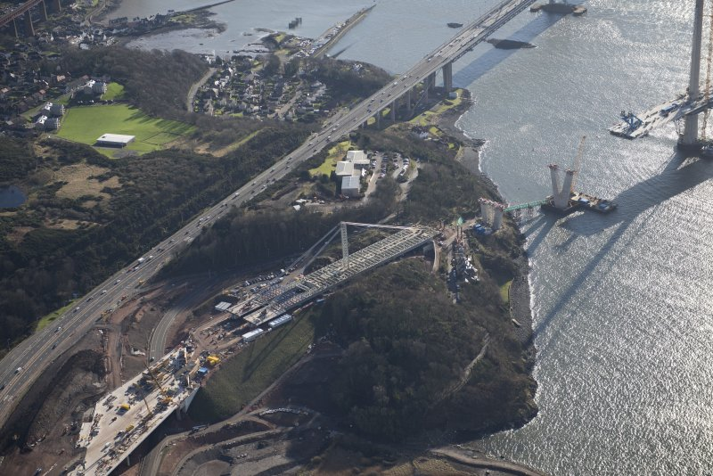 Oblique aerial view of the construction of Queensferry Crossing on the north bank, looking SE.