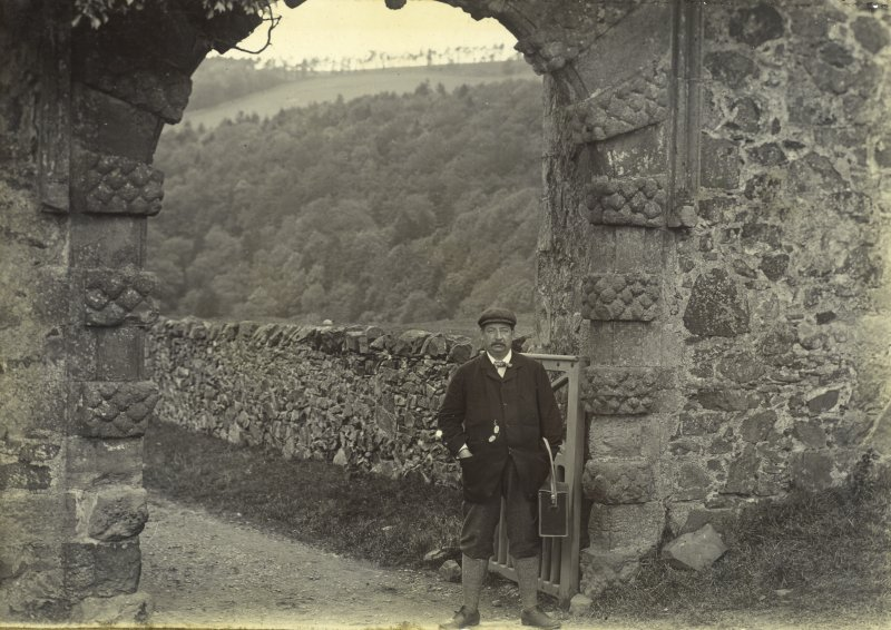 View of Neidpath Castle entrance gateway, with man carrying photographer's bag
