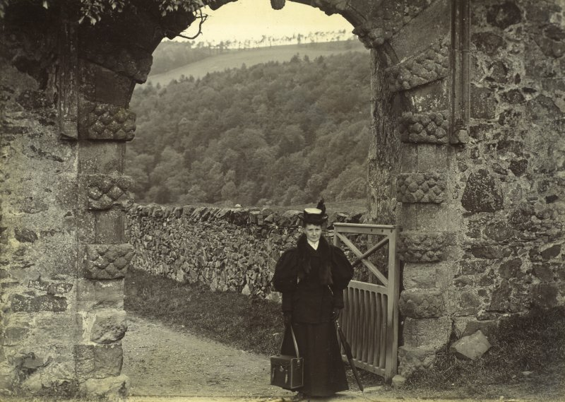 View of Neidpath Castle entrance gateway, with lady carrying photographer's bag