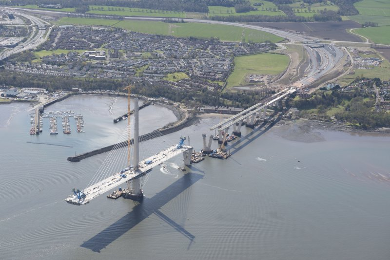 Oblique aerial view of the construction of the Queensferry Crosssing at the south bank of the River Forth, looking SE.