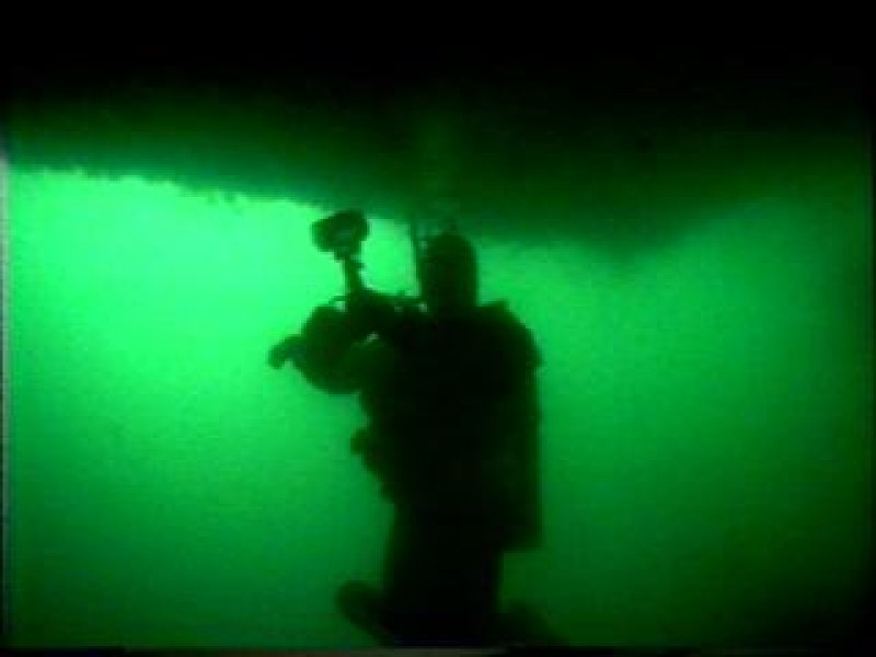 Photograph of diver under stern of HMS Breda