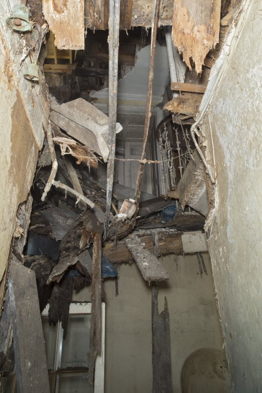 Ground floor, corridor, view looking through collapsed ceiling to 1st floor landing above