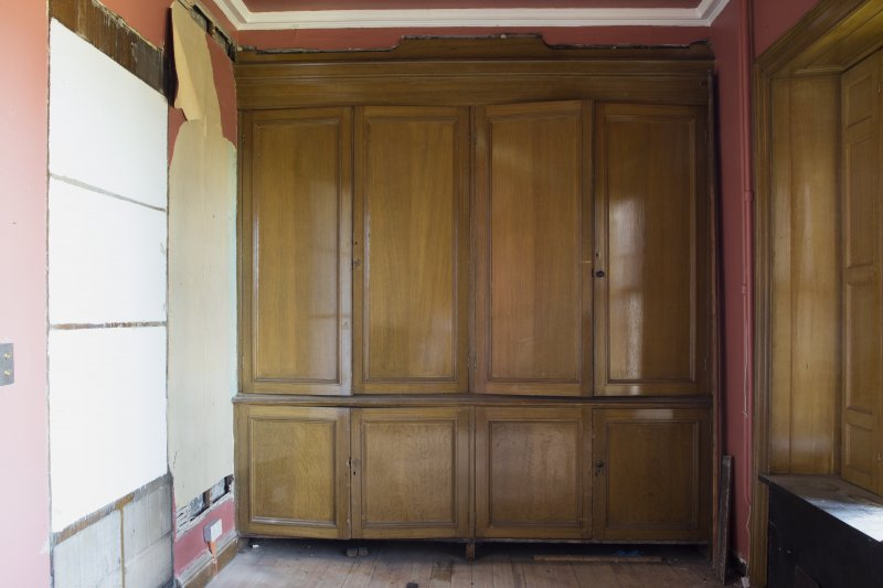 Ground floor. North room (library). Detail of bookcases. Door closed.