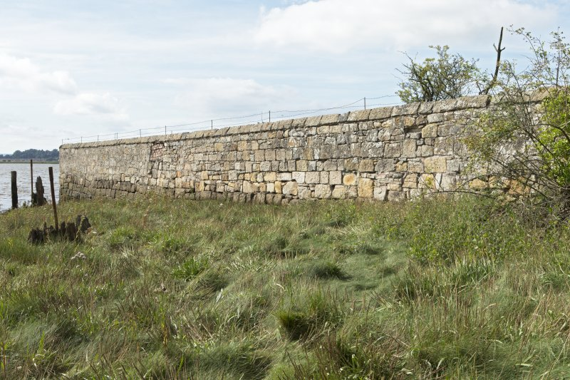 Walling on west side of estuary, view from north east. Note the lower, darker-coloured stone courses of the original quay wall.
