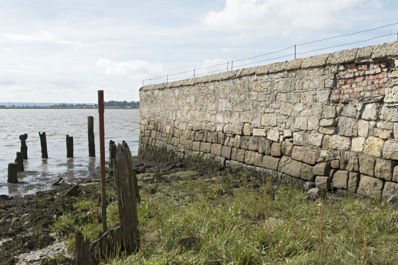 Walling on west side of estuary and remains of timber wharf posts, view from north east. Note the lower, darker-coloured stone courses of the original quay wall.