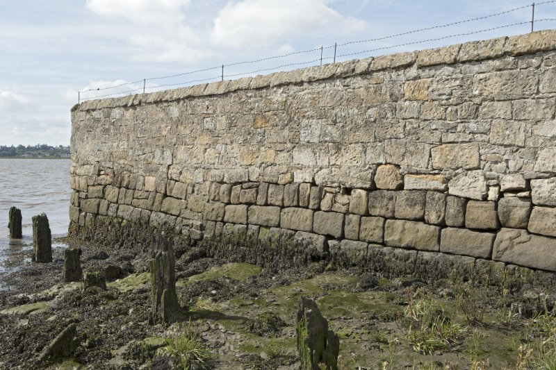 Detail of walling and remains of timber wharf or quay posts on west side of estuary. Note the lower, darker-coloured stone courses of the original quay wall.