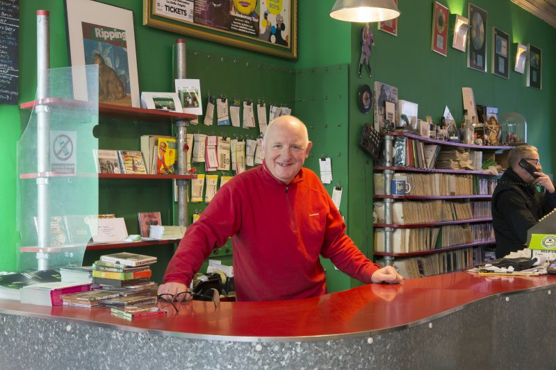 Portriat of owner, John Richardson behind counter.