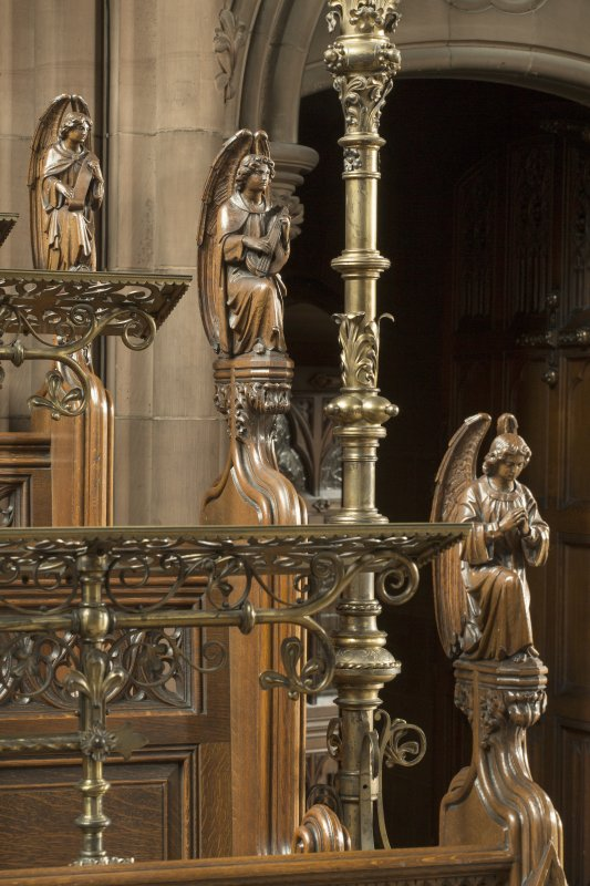 Chancel. Detail of three carved angels on ends of choir stalls.