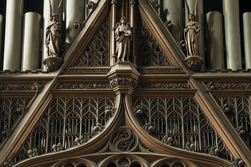 Chancel. Detail of carved angels in front of organ pipes.