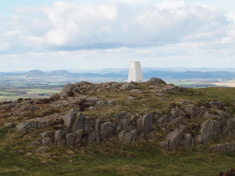 View of summit and triangulation pillar, with the Eildon Hills in the background.