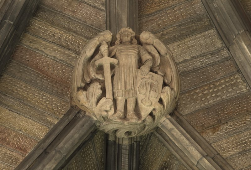 Choir, ceiling, detail of carved boss (angel with sword and shield)
