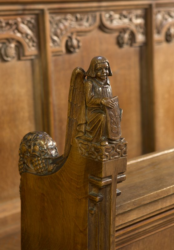 Choir, detail of carved angel with shield on choir stalls