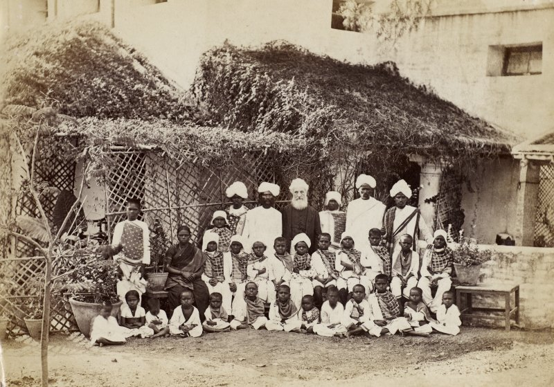 Group of local people, including children posed outside a building with bearded man.  Possible mission station. Untitled and unknown location.  Photograph Album No.25: Mr Dog Album.
