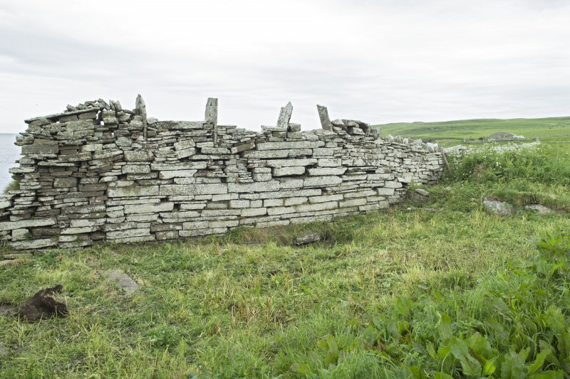 W wall of E building, view from south east. The wall is topped by a later stone dyke