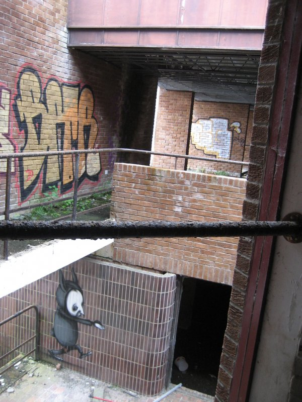 General view of main stairwell with multiple graffiti images.