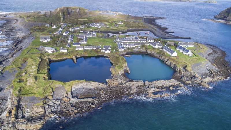 Oblique aerial view showing East and Midd-Engine quarries and Easdale Village and Harbour.
